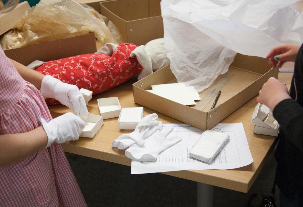 Lapset askartelevat pahvista valkoisia pieniä laatikoita. Pöydällä on pakkausmateriaalia ja isoja pahvilaatikoita.