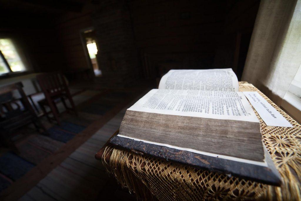 Aukinainen vanha ja paksu kirja esillä hämärässä huoneessa.