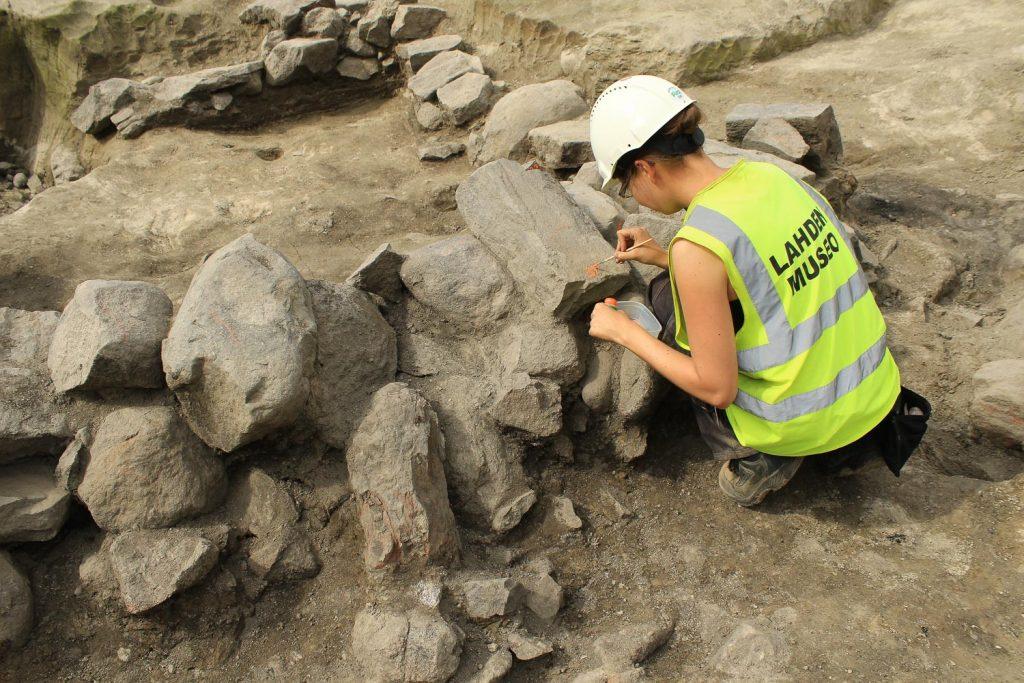 Suojaliiviin ja kypärään pukeutunut arkeologi on kyykistynyt kivirakenteen viereen merkitsemään rakenteen kiviä.