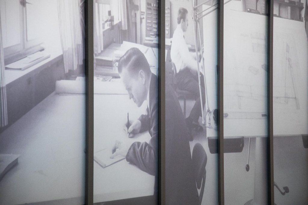 Mies työskentelee tarkkaavaisesti toimistossa kynän ja lehtiön ääressä.