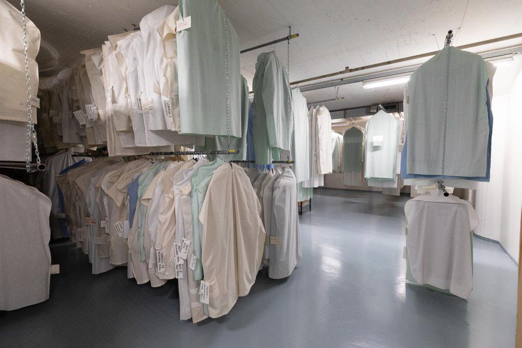 Pukupusseissa roikkuvia vaatteita rekeissä tekstiilivarastossa.