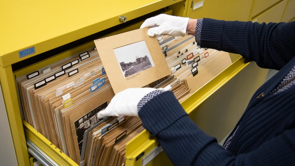 Museotyöntekijä tutkii mustavalkoista valokuvaa, jonka hän on ottanut keltaisesta arkistokaapista.