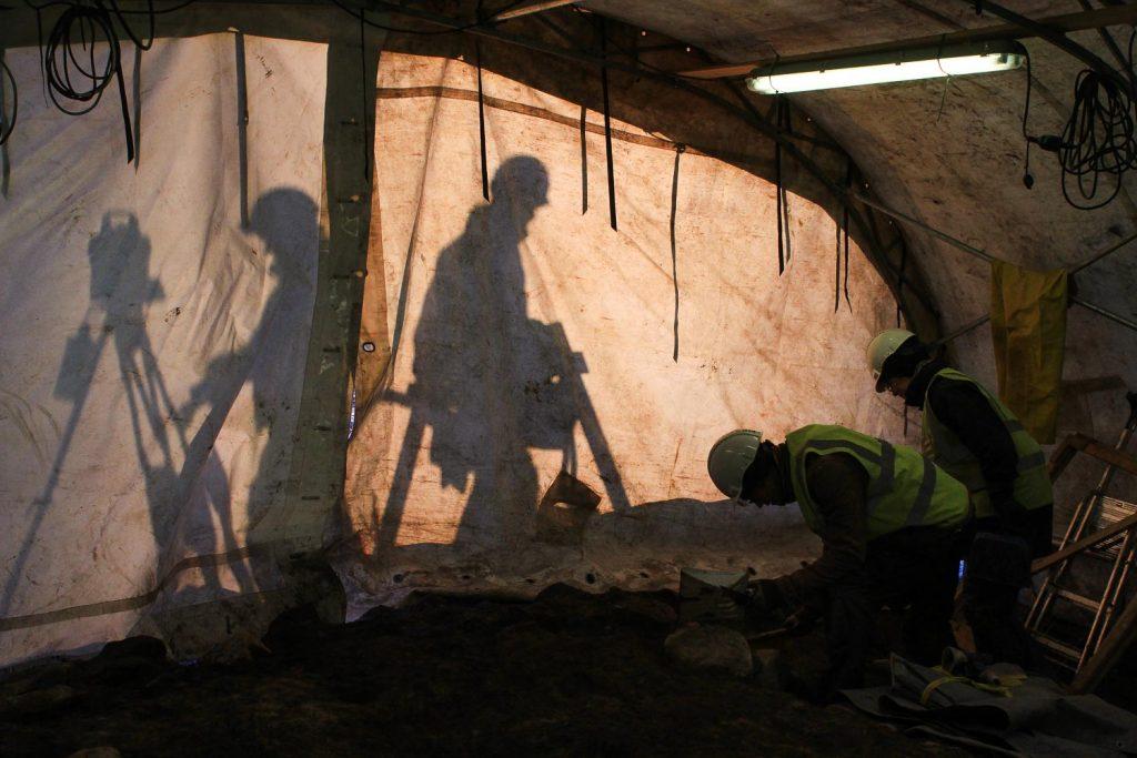 Arkeologisen kaivauksen työntekijät työskentelevät teltan sisällä. Valo muodostaa siluetin teltan ulkopuolisista ihmisistä.