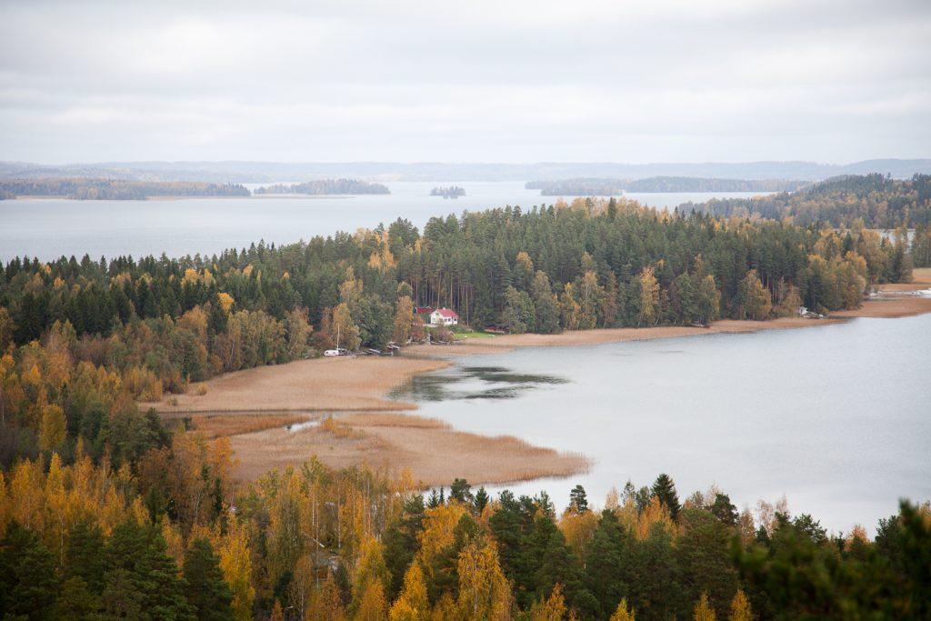 Pilvisenä päivänä korkealta kuvattu laaja järvimaisema, jossa saaria ja metsää, sekä kaukana pieni talo.