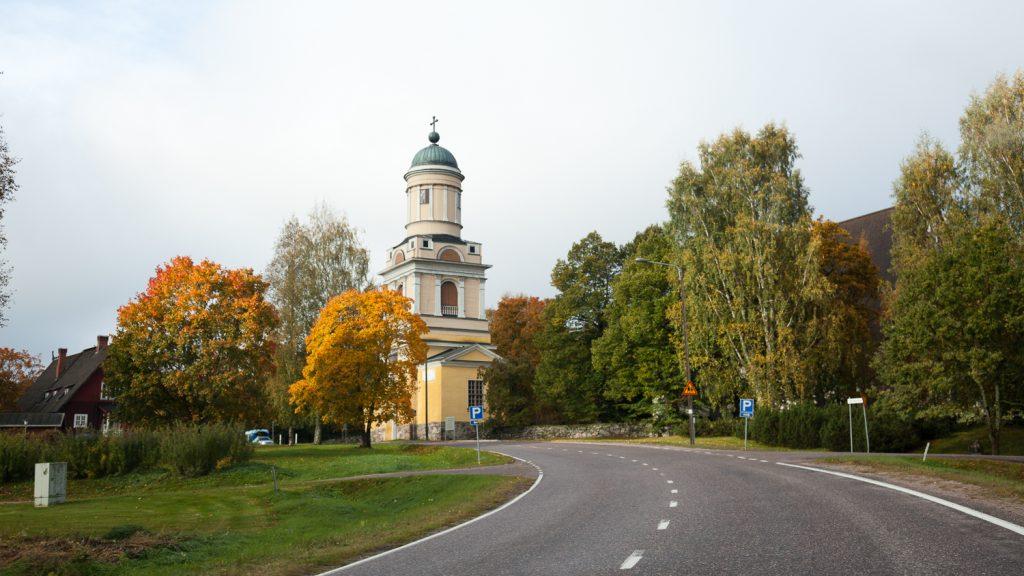 Kuvan keskellä on kellertävä kirkon kellotapuli, jonka ympärillä on lehtipuita ja edustalla tie.