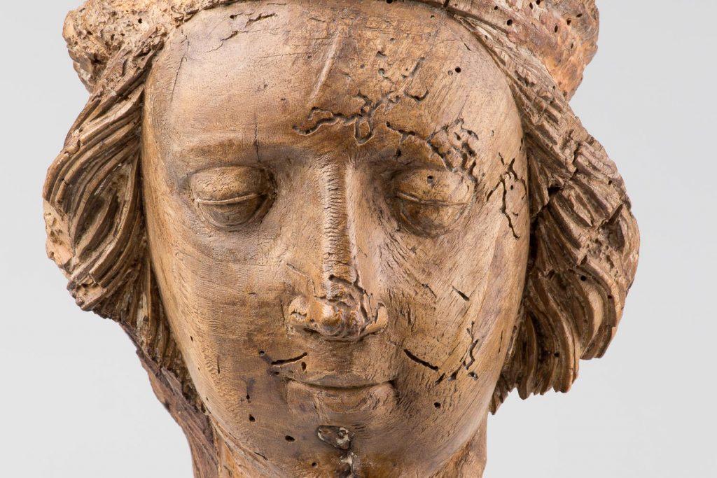 Wooden sculpture of a face of a human.