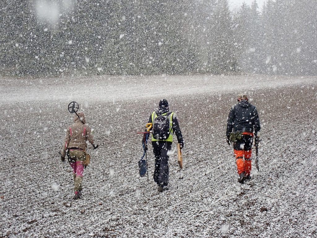 Arkeologit kävelevät pellolla sankassa lumisateessa.