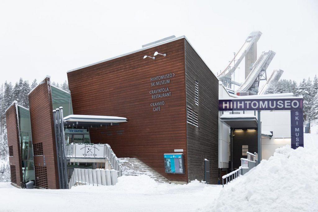Talvinen Hiihtomuseorakennus. Taustalla Lahden hyppyrimäet ja lumiset puut.