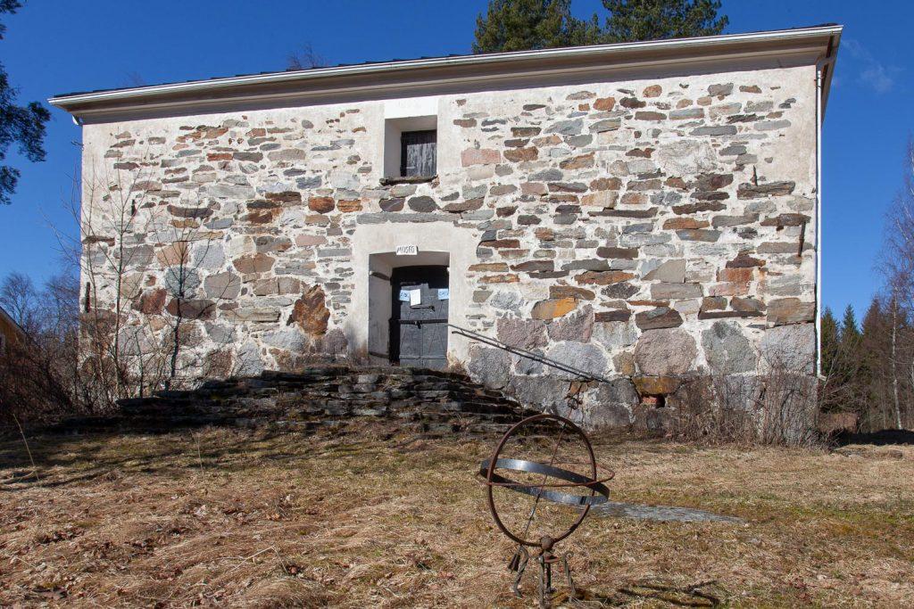 Kivistä muurattu ja osin valkoiseksi kalkittu makasiinirakennus, jonka edustalla on kuivuneessa heinikossa aurinkokello.
