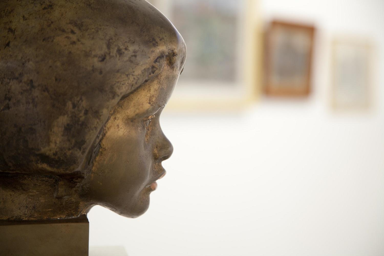 Lähikuva työtön päätä esittävä veistoksen sivuprofiilista Orimattilan taidemuseossa, taustalla maalauksia.