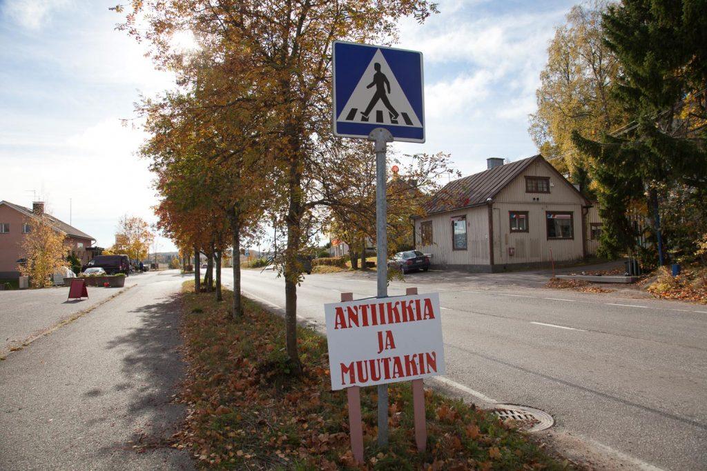 Kylänraitti, jossa varrella koivuja, rakennus ja etualalla kyltti jossa lukee Anttiikkia ja muuta.