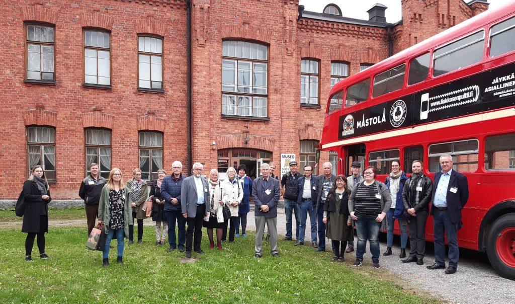 Joukko ihmisiä valokuvattavana punaisen kaksikerroksisen bussin edessä. Taustalla punatiilinen museorakennus.