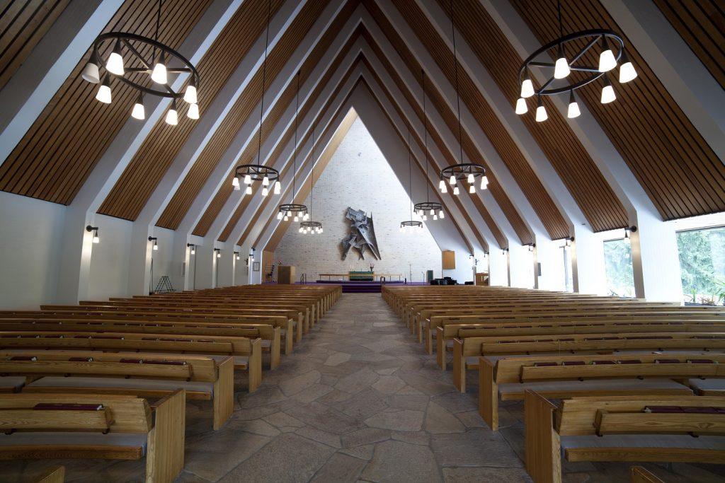 Kirkkosali, jossa penkit käytävän molemmin puolin ja keskellä alttari ja veistos.