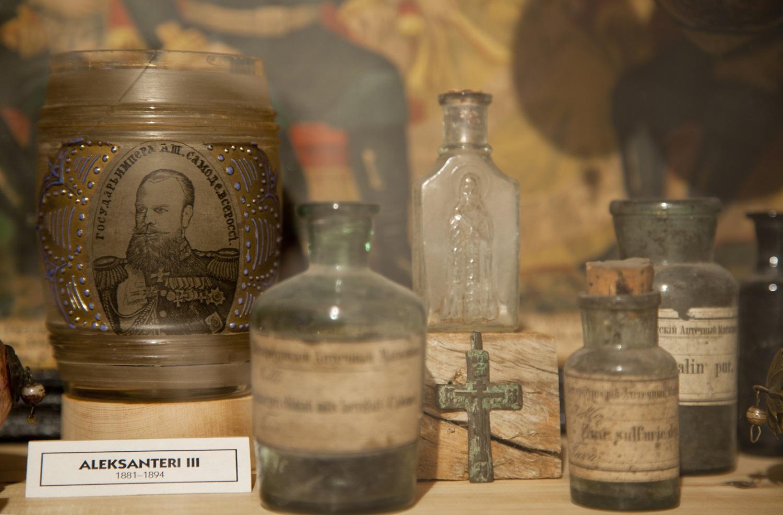 Pulloja ja lasiesineitä Orimattilan pullomuseon näyttelyssä.