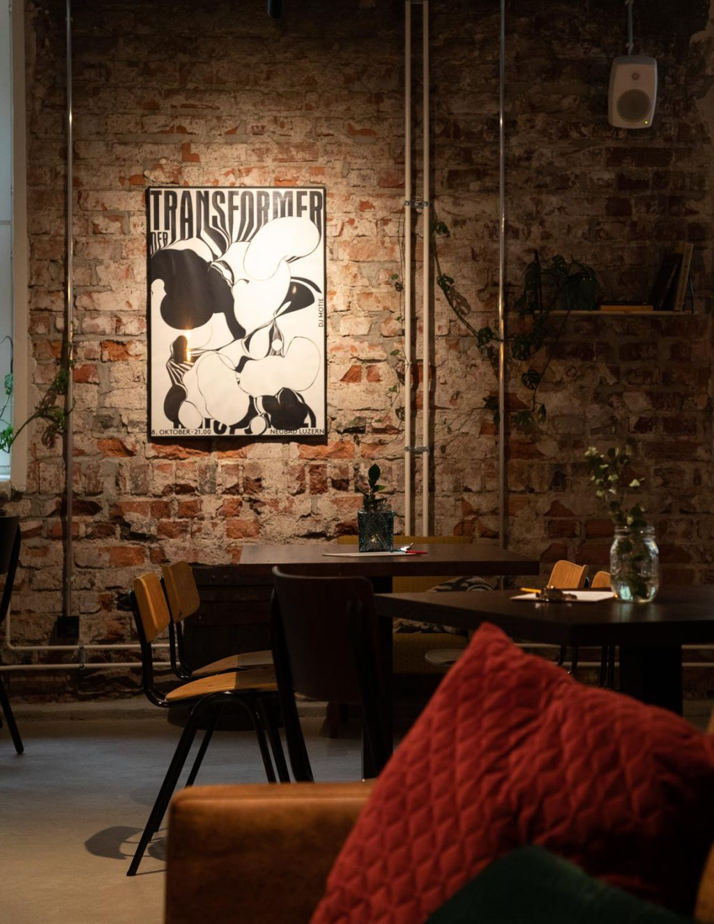 A restaurant. Table groups, mood lighting, a poster on a brick wall. An old radio on a windowsill.