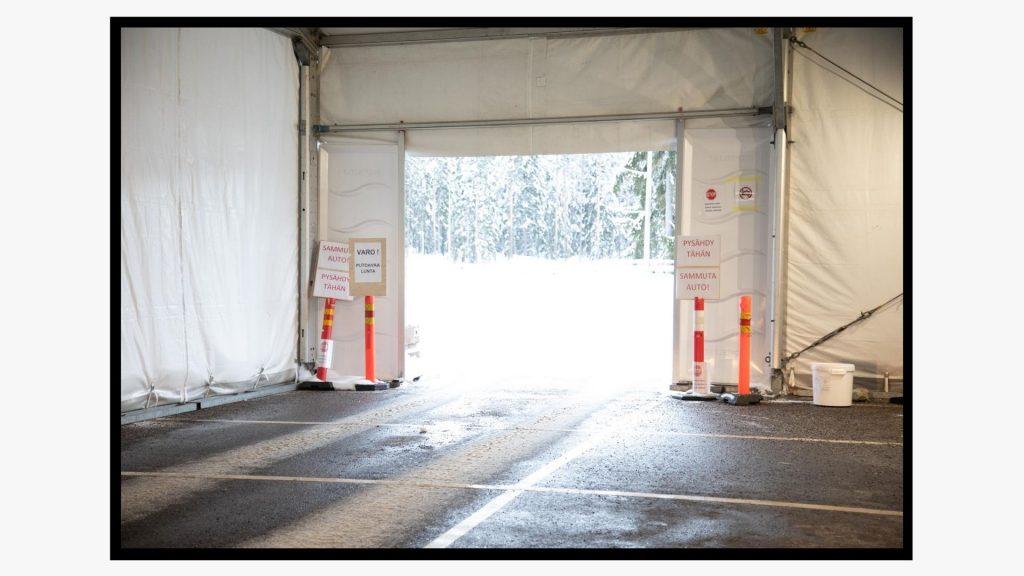 Autolla läpi ajettavan koronatestauspisteen teltan oviaukosta näkyy lumisia puita.