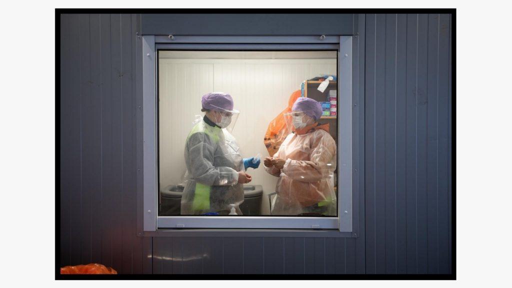 Kaksi suojavarusteisiin ja -maskeihin pukeutunutta koronatestauspisteen työntekijää kuvattuna ikkunan läpi.