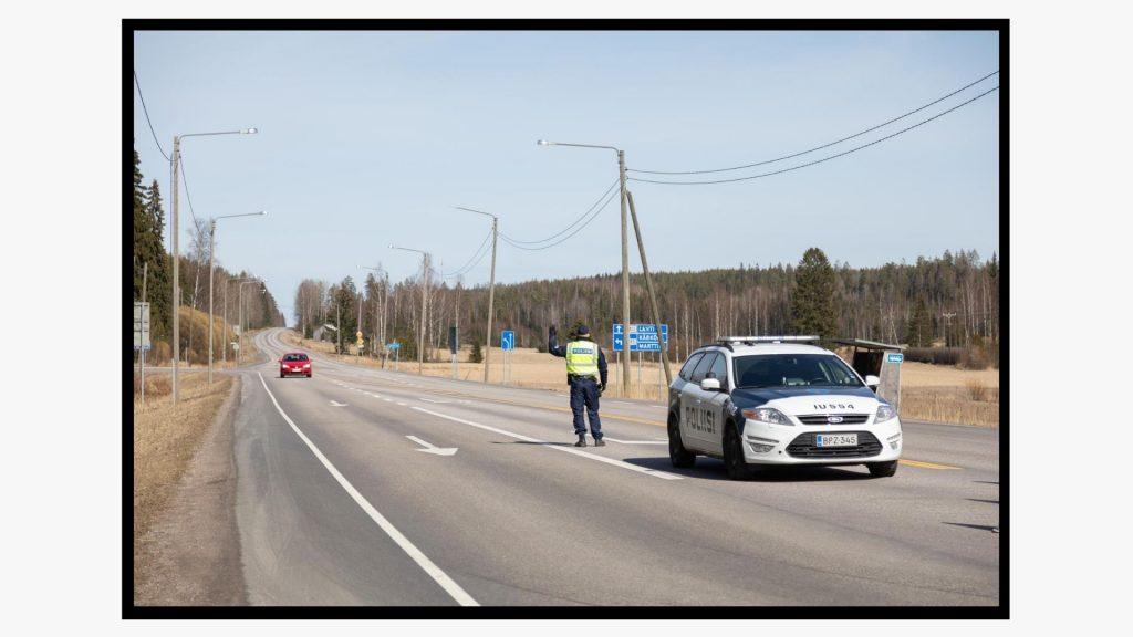 Suojaliiveihin pukeutunut poliisi valmistautuu pysäyttämään auton Uudenmaan ja Päijät-Hämeen maakuntien rajalla.