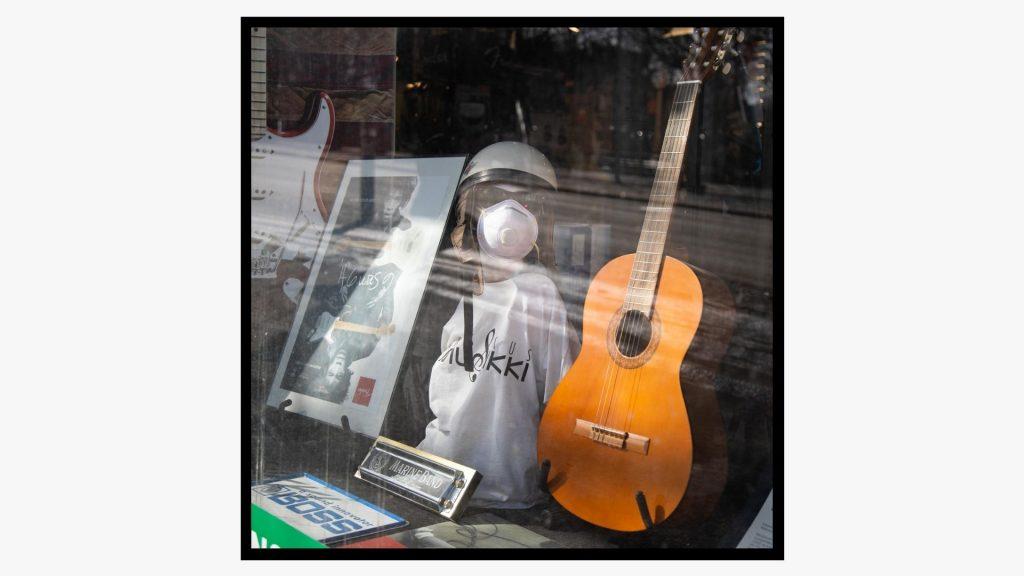Musiikkiliikkeen näyteikkunassa mallinukella on päässään kypärä, aurinkolasit ja kasvomaski.