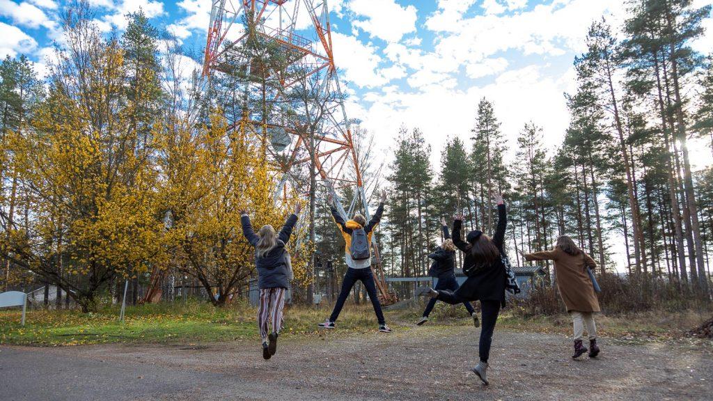 Ihmiset hyppäävät, takana radiomasto.